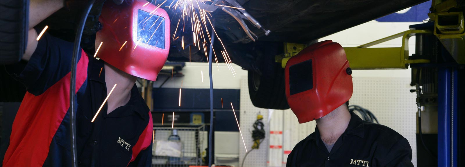 Sparks fly as MTTI Auto Mechanic Instructor and student are welding the underside of a car on a lift.