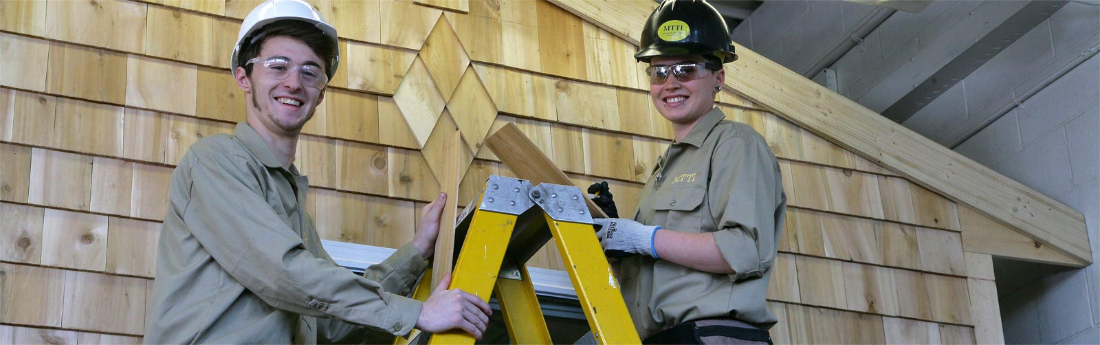 Two students on a ladder in front of the cedar-shingled side of a home module they built