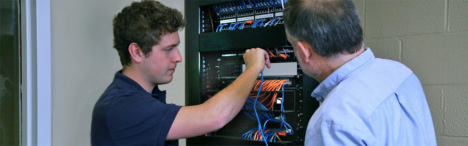 Student and Computer Instructor at network rack in training lab.