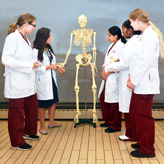 MTTI Instructor, Courtney Olson, With Students Examining A Skeleton.