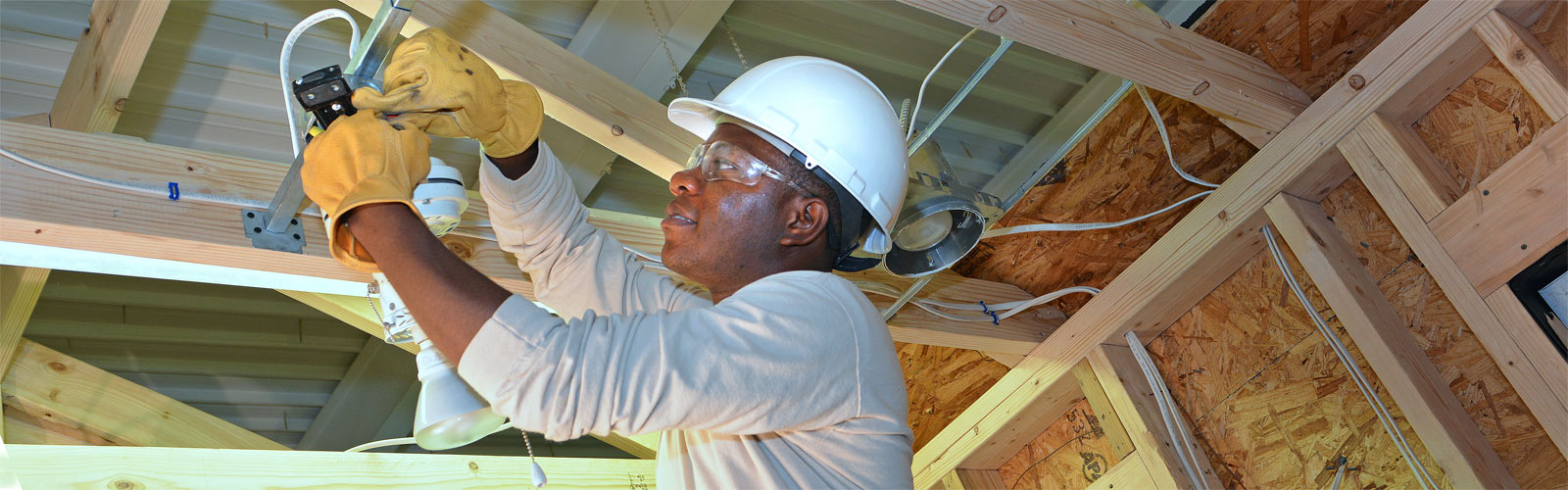 Student wearing hard hat and gloves wiring a ceiling light in electrical training module.