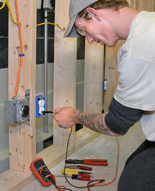 Electrical student at MTTI installing an outlet.