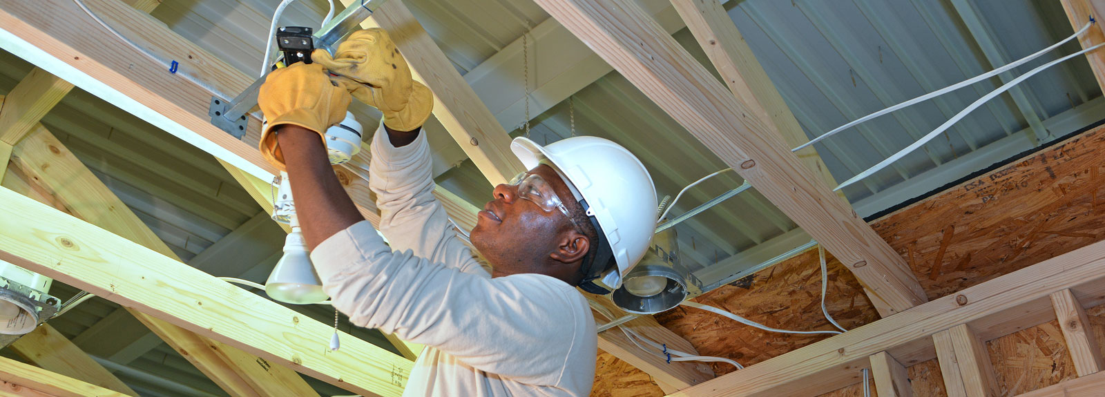 MTTI Student Installing Electrical Lighting On Overhead Framing In House Module