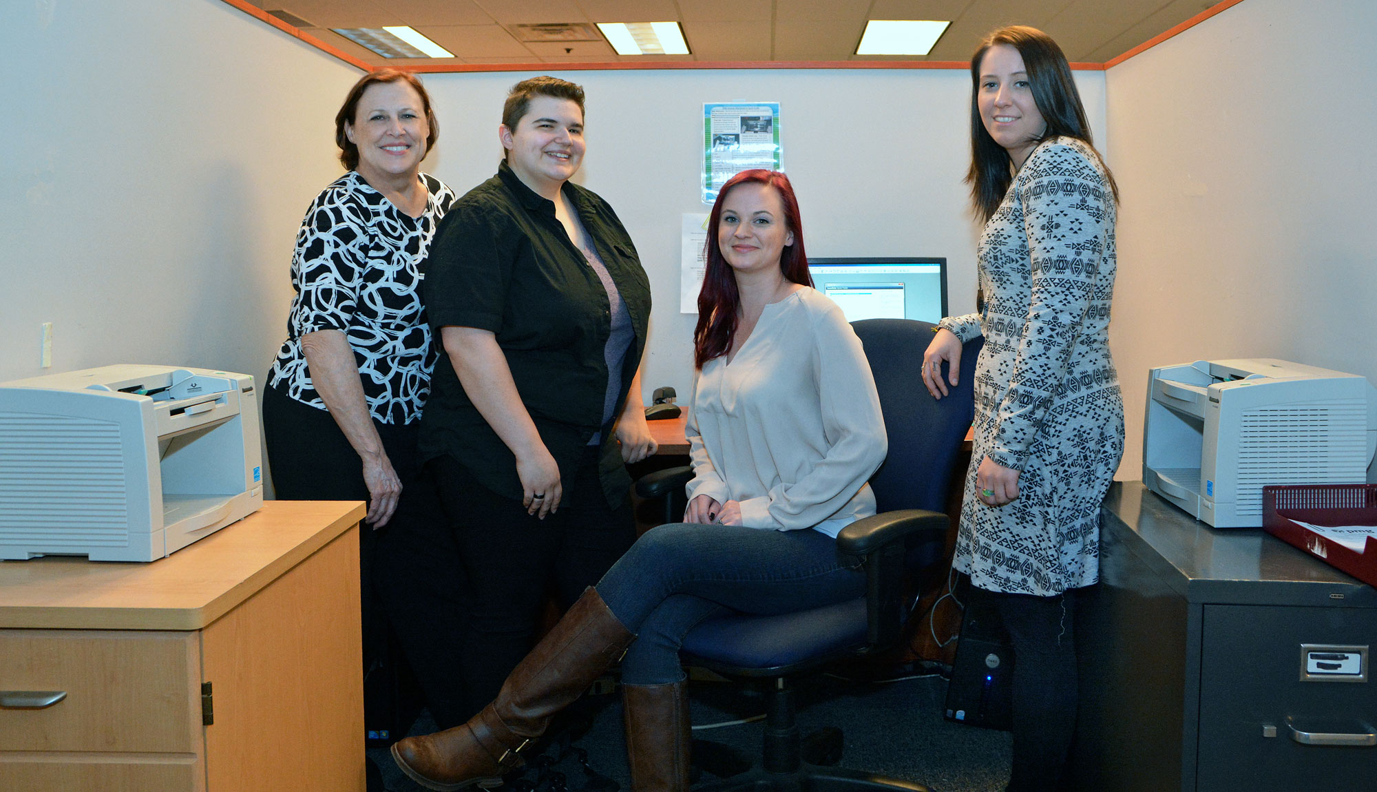 Four MTTI 2015 Medical Billing and Coding Graduates, who work at PMG, pose for a picture.
