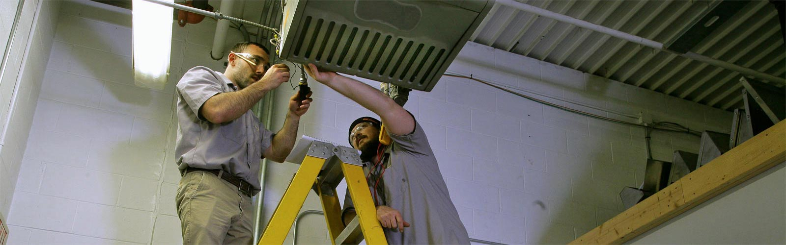 Two MTTI HVAC/R students on ladders repairing a heating unit.