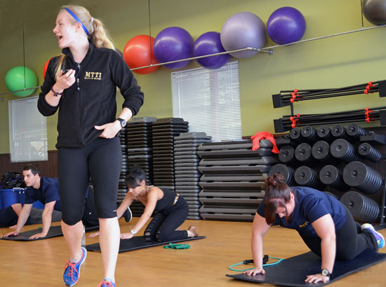 Female Fitness Trainer student leading class in exercise.