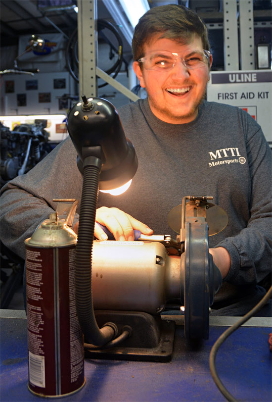 Kevin Breault Grins, While Using The Grinder In MTTI's Motorcycle Shop.