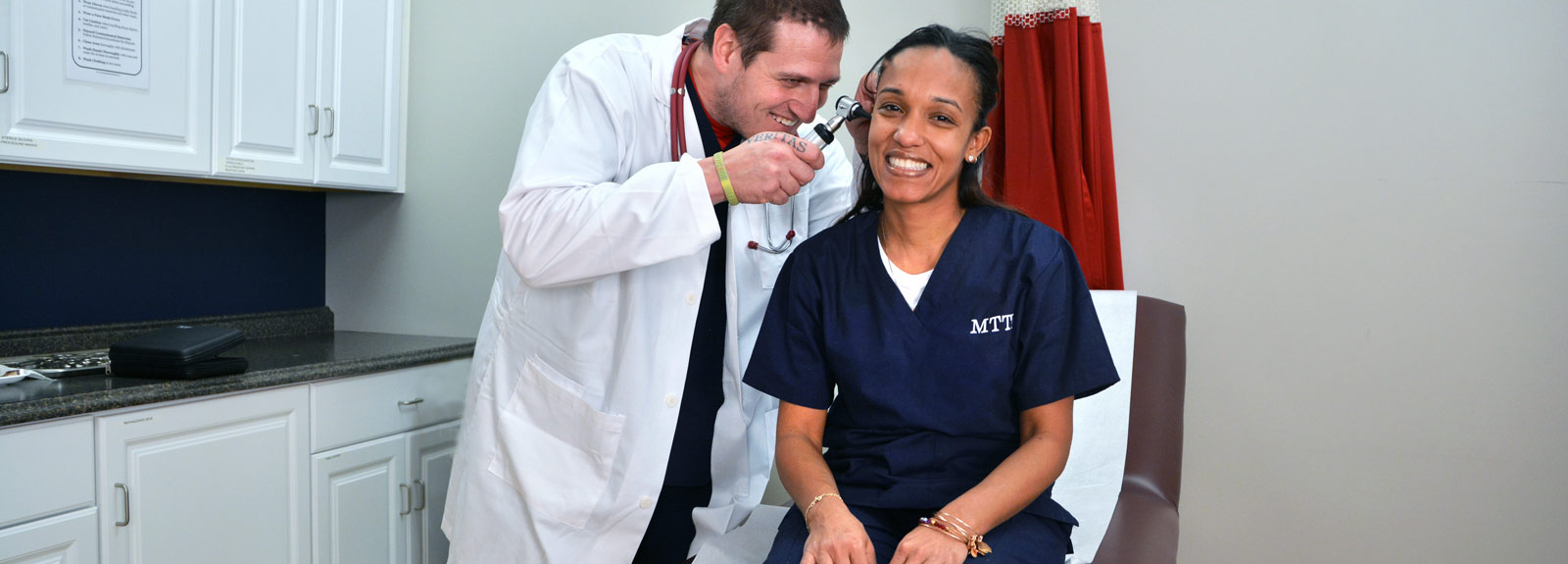 Medical Assistant Student Using An Otoscope To Examine Another Student's Ear