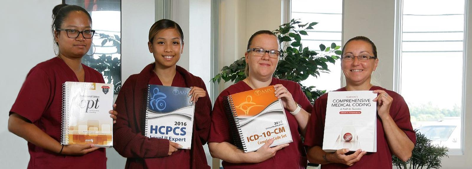 MTTI Medical Billing & Coding students holding hospital and health care coding text books.