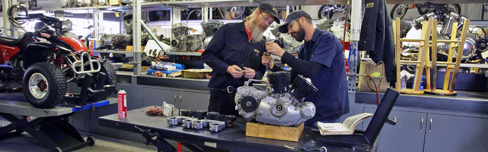 Instructor and student working on engine in MTTI's motorcycle tech shop.
