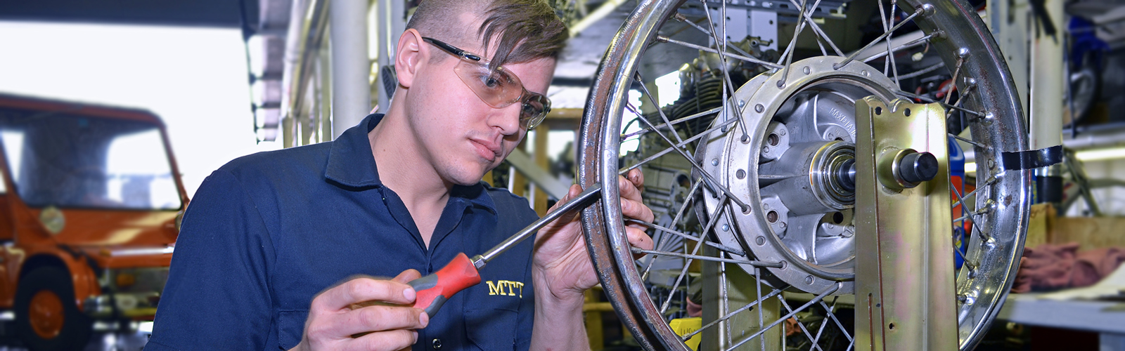 Young man repairing motorcycle wheel in MTTI's shop.