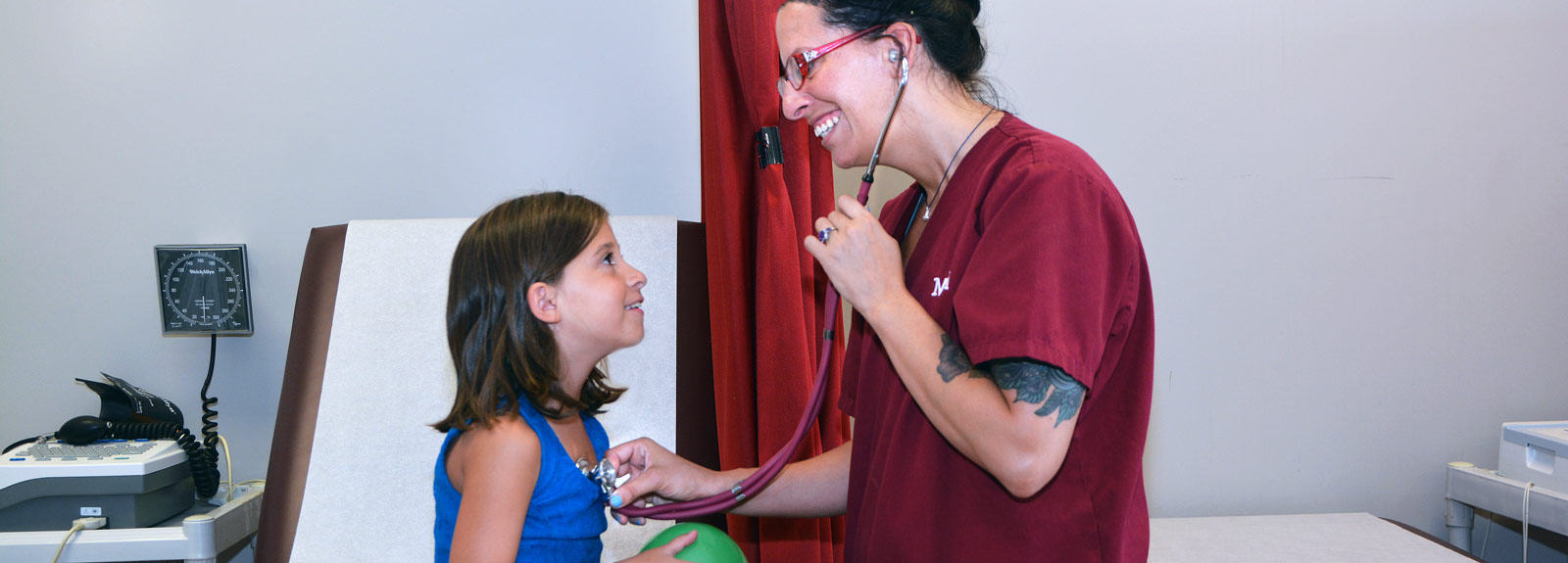 Female Medical Assistant student using stethoscope to listen to a child's heart.