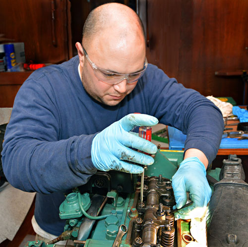 MTTI Graduate, Adam Zimbo, working on a boat engine.