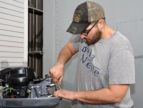MTTI Graduate Jon Carvalho, working on an outboard engine.
