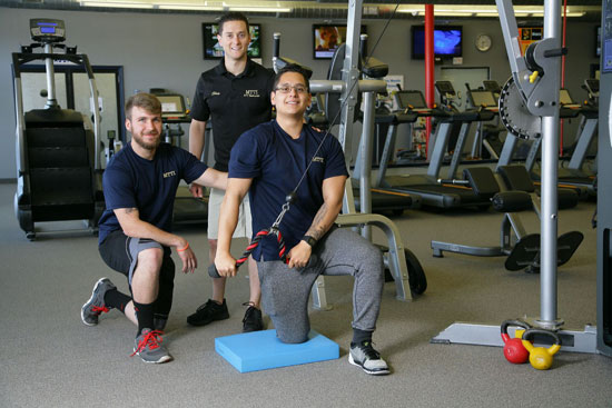 Two male students with Fitness Trainer Instructor in the gym.