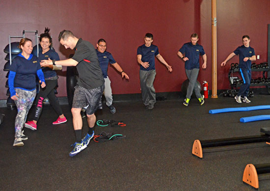 Fitness Trainer Instructor leading class in an exercise.