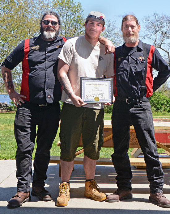 Robbie Thorp With His Motorcycle Technician Instructors Outdoors At Graduation.