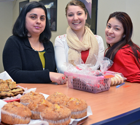 Three female students hoisting a bake sale at the school.