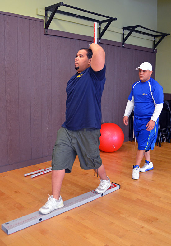 Guillermo & Alvin Practice Conducting a Functional Movement Screen (FMS).
