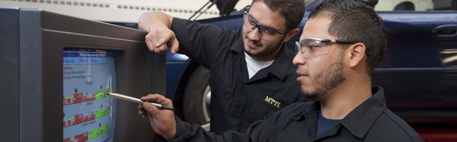 Two Auto Tech students looking at the car alignment diagnostics on a computer screen