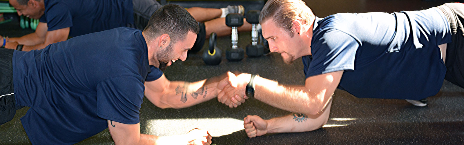 Two MTTI Personal Fitness Trainer students engaged in fitness exercise together.
