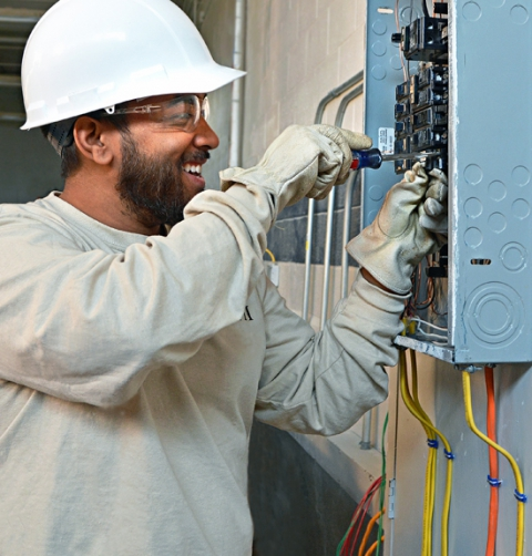 MTTI student wearing hardhat and safety gloves is wiring an electrical panel.